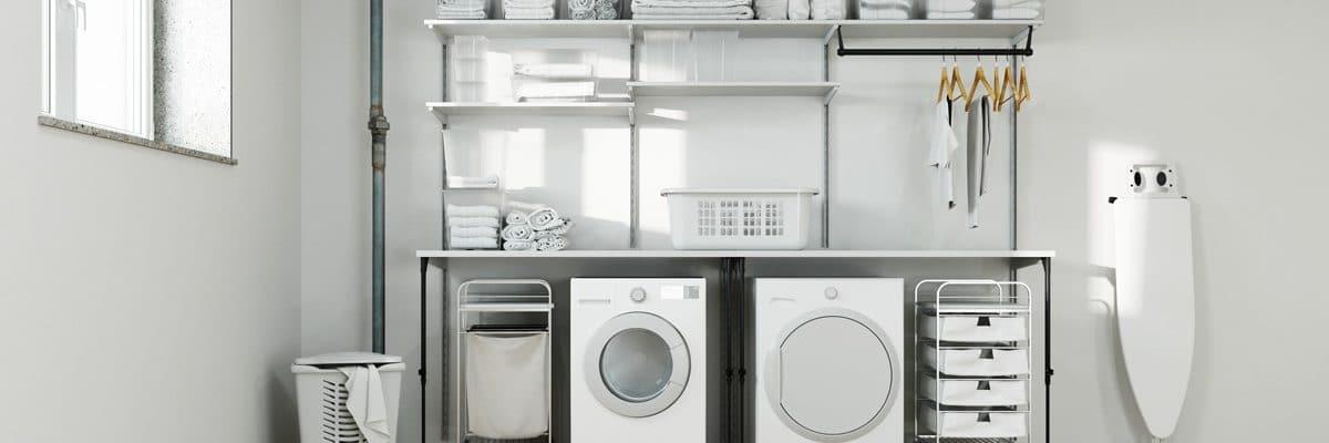 Une buanderie blanche avec lave-linge, sèche-linge et la table à repasser