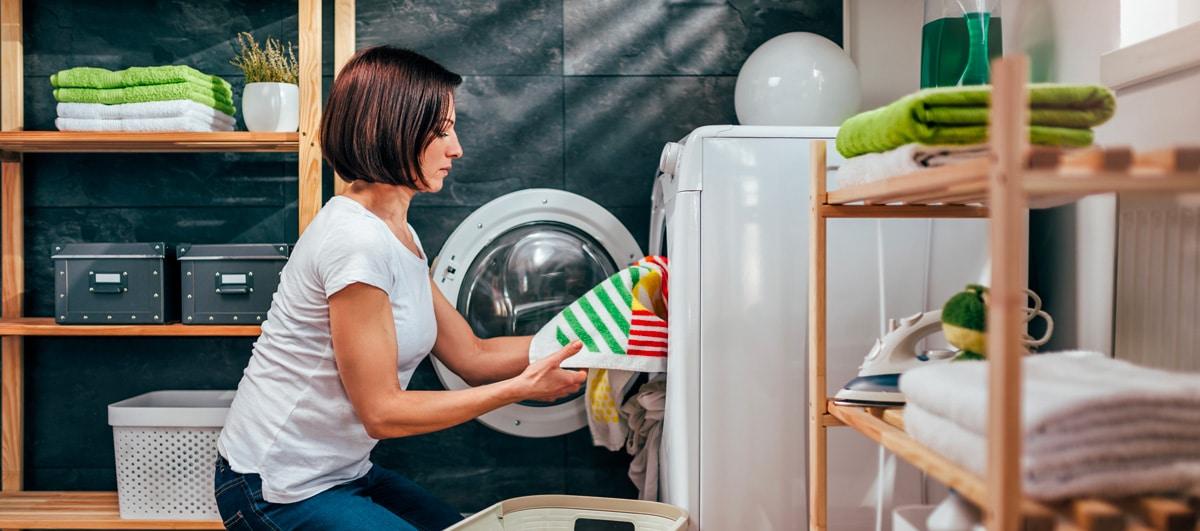 Une femme sort le linge du lave-linge qui attend d'être séché au sèche-linge