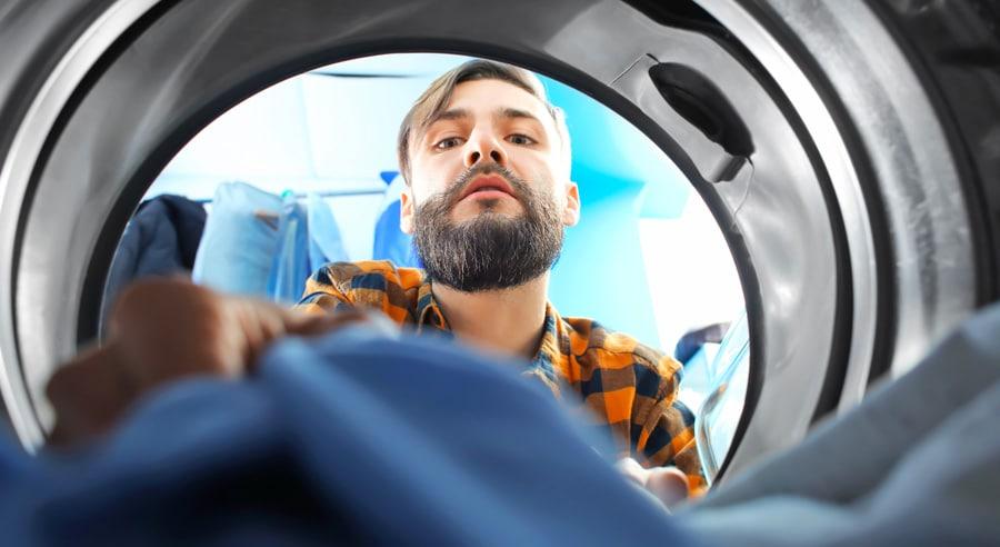 Un homme récupère du linge sec et chaud dans un sèche linge condensation