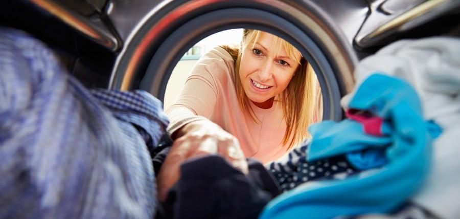 Une femme blonde est heureuse de découvrir son linge séché avec un sèche-linge à condensation
