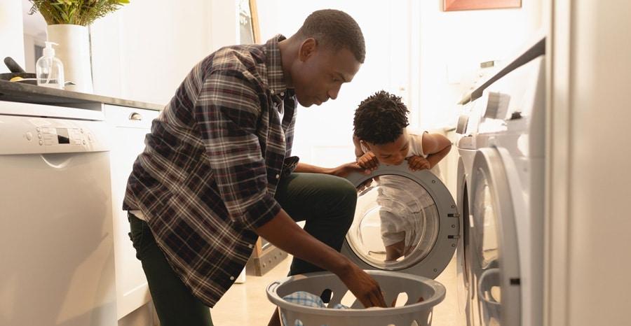un père et son fils pendant le nettoyage et le séchage du linge