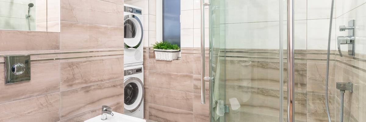 Un salle de bains design avec un sèche linge superposé à un lave linge grâce à un kit de superposition