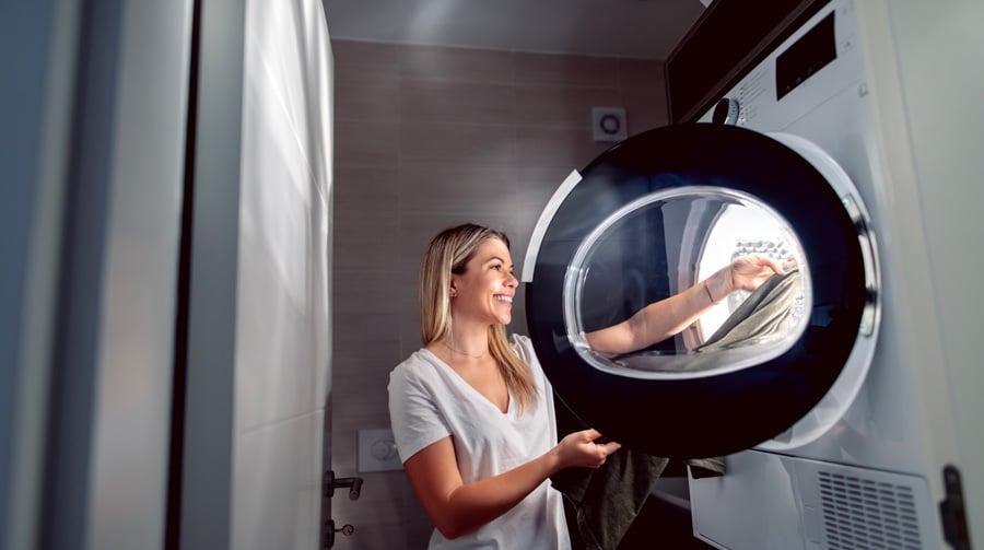Une femme blonde sèche du linge dans un sèche-linge de grande capacité de poids de linge