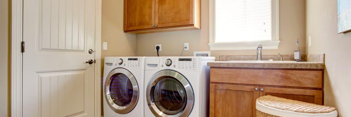 machine à laver et sèche-linge dans une buanderie boisée