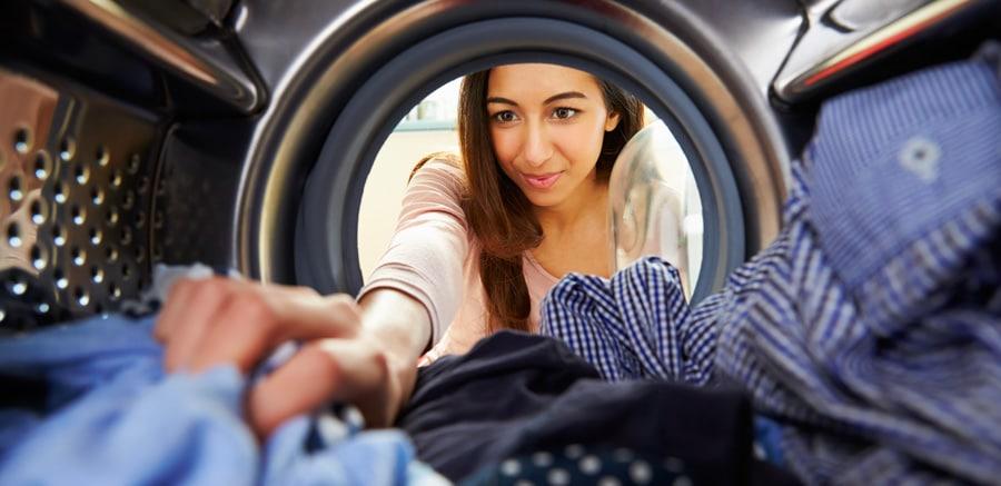 Une femme récupère du linge sec dans le tambour d'un sèche-linge